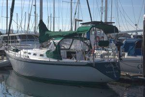 white and green sailboat at dock